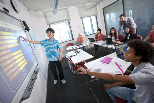 Students and teachers using the interactive whiteboard at Embassy.