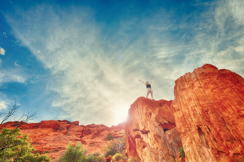 Woman Standing On Red Rocks Celebrating Success-2
